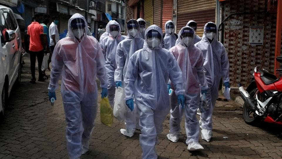 Healthcare workers wearing personal protective equipment (PPE) walk towards different localities before the start of a check-up camp for the coronavirus disease (Covid-19) in Mumbai.