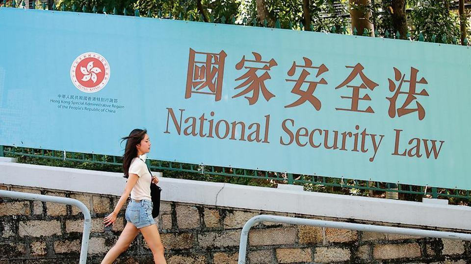 A woman walks past a banner promoting the controversial national security law in Hong Kong on Tuesday.