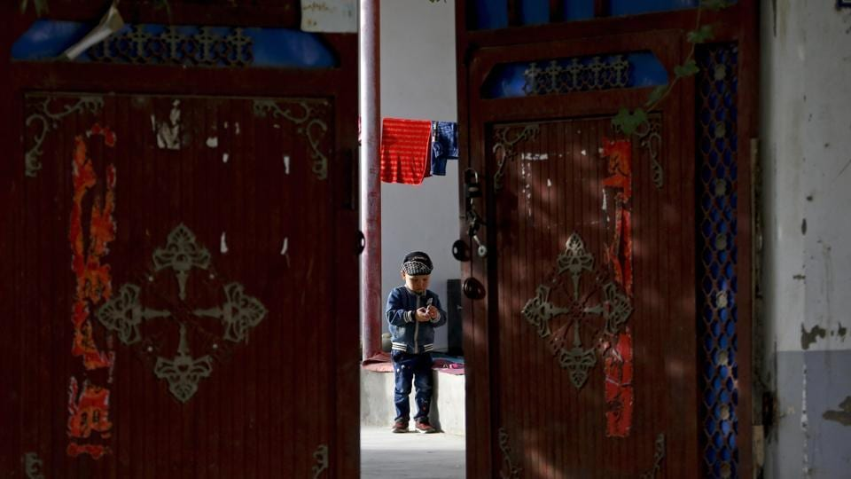 In this 2018 photo, a Uighur child plays alone in the courtyard of a home at the Unity New Village in Hotan, in western China's Xinjiang region.