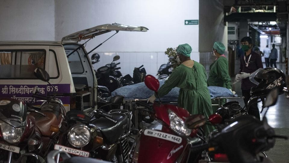 The medical staff of a private hospital transfer a dead body into an  ambulance.