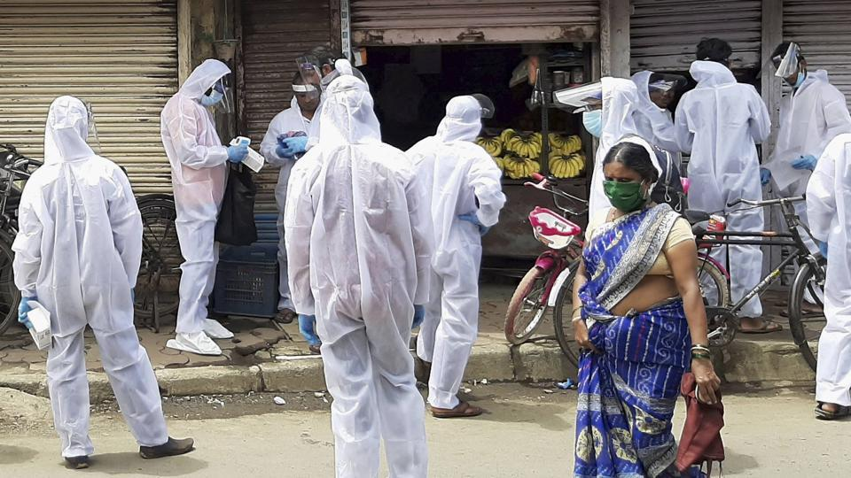 Civic officials wearing protective suits conduct door-to-door thermal screening of the residents of Kurar area in the wake of coronavirus pandemic, at Malad in Mumbai on Monday.