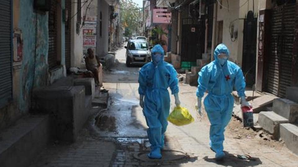 Health workers in PPE coveralls arrive to collect samples for coronavirus testing in Gurugram.