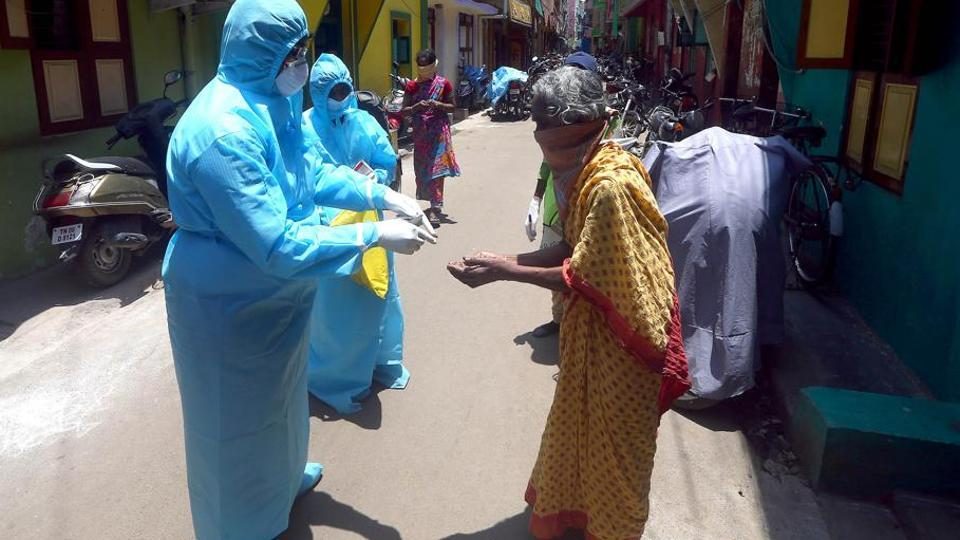 Health workers wearing protective gear check the temperature of a woman during a door-to-door verification of people in Chennai.