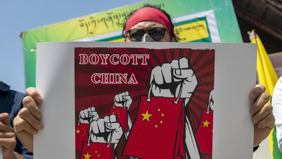 An exile Tibetan activist holds a banner during a street demonstration by the Tibetan Youth Congress asking for a boycott of Chinese goods in Dharmsala, India