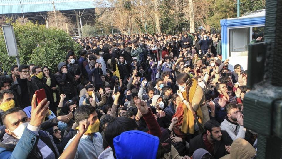 In this 2017 file photo , university students attend a protest inside Tehran University while anti-riot Iranian police prevent them to join other protestors, in Tehran, Iran.