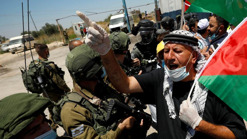 A demonstrator holding a Palestinian flag gestures in front of Israeli forces during a protest against Israel's plan to annex parts of the occupied West Bank, in Haris.