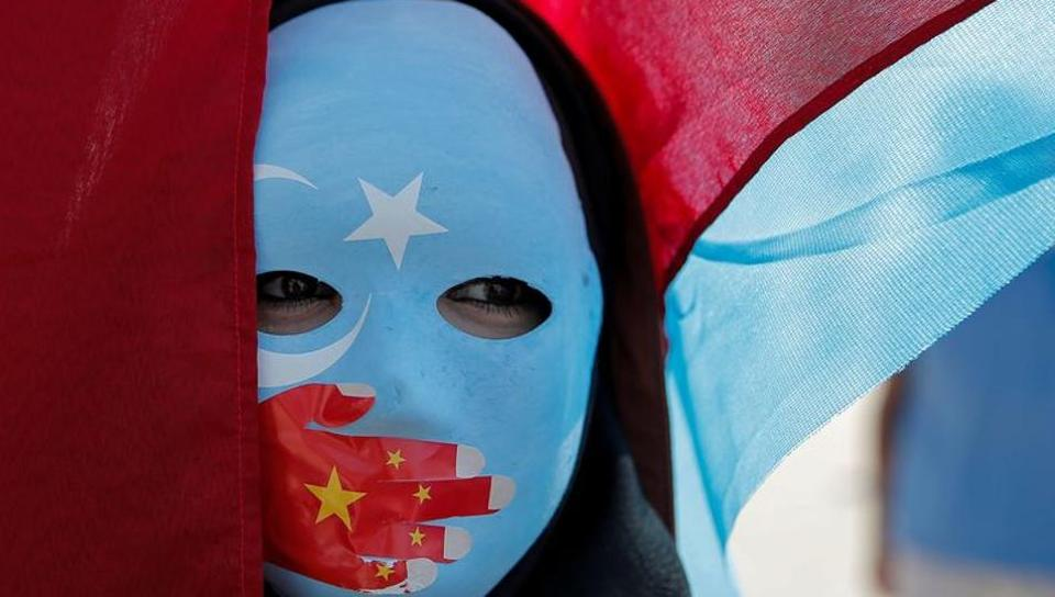 In this file photo, an ethnic Uighur demonstrator wears a mask as she attends a protest against China in front of the Chinese Consulate in Istanbul.