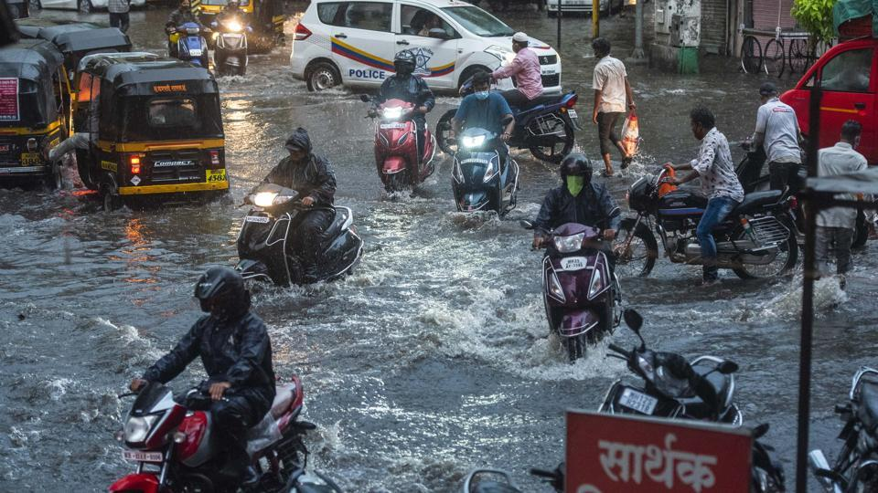 Commuters wade through a waterlogged area at Narpatgiri chowk, Mangalwar peth in Pune, India, on Monday, June 29, 2020.