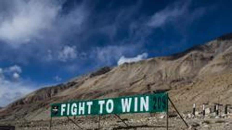 An Indian Military banner post is seen on the road to Pangong Lake