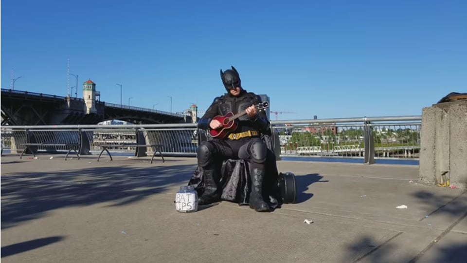 The image shows a person dressed as Batman playing ukulele.
