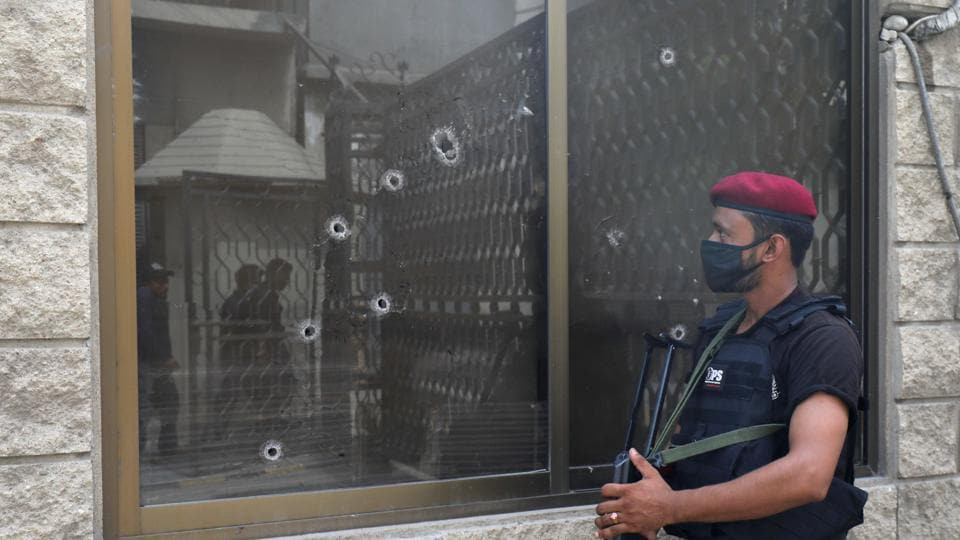 A police officer stands guard next to a bullet-riddled window at the Pakistan Stock Exchange building after an attack in Karachi, on June 29.