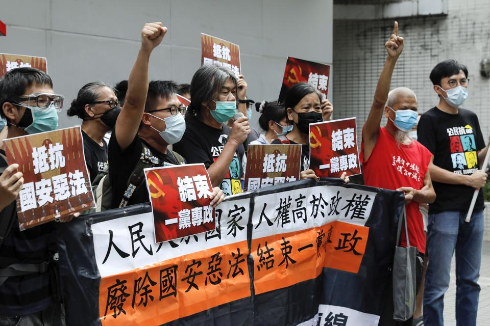 Pro-democracy Leung Kwok-hung, center, and others protesters shout slogans