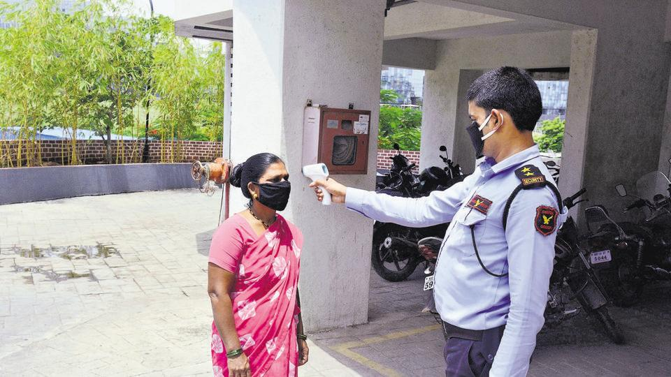 A security  guard of a society in Kharadi checks the temperature of a maid before she enters a residential society.