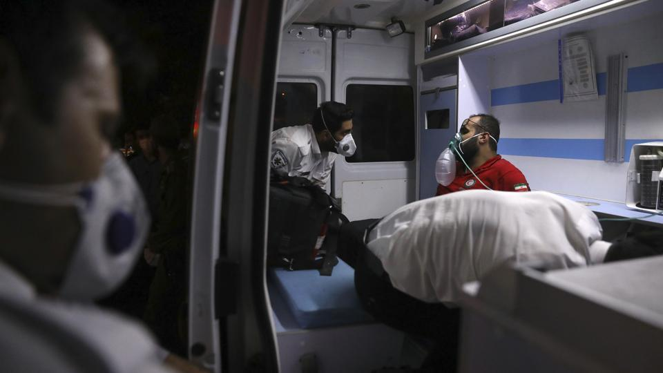 A rescue worker receives oxygen in an ambulance after he was overcome by smoke from the explosion of Sina Athar Clinic in Tehran, Iran, early Wednesday, July 1, 2020.