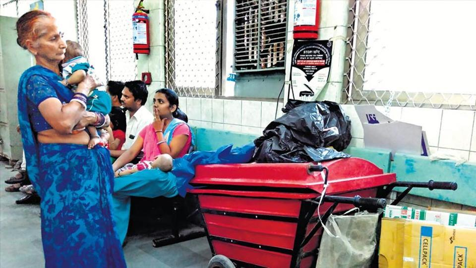 Patients wait near a pile of hazardous bio-medical waste at the Kalawati Saran Hospital .