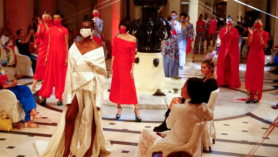 Models wear face masks as they present creations of the 2021 summer collection by designer Anja Gockel at Adlon Hotel, following the coronavirus disease (COVID-19) outbreak in Berlin, Germany, June 30, 2020.  (REUTERS)