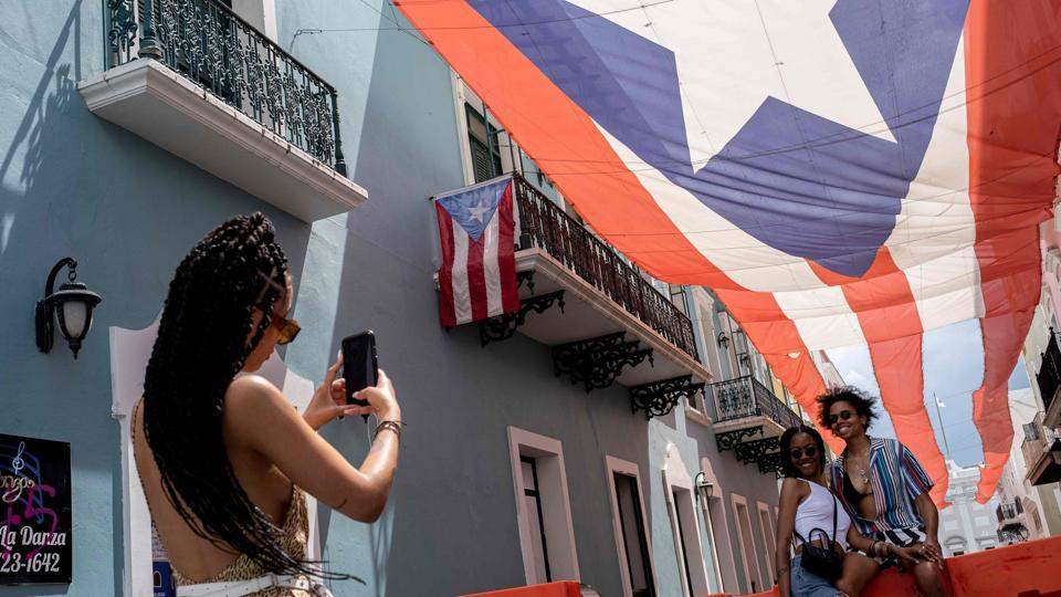 A tourist takes photos of a couple in front of the Governor's mansion in San Juan, Puerto Rico on June 30, 2020, during the coronavirus pandemic.