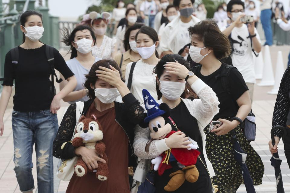 People wearing face masks to protect against the spread of the new coronavirus walk toward the entrance to Tokyo Disneyland in Urayasu, near Tokyo, Wednesday, July 1, 2020. Tokyo Disneyland reopens for the first time in four months after suspending operations due to coronavirus concerns.  (AP)