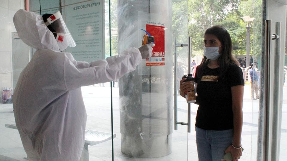 A woman undergoes thermal screening at the entrance of a shopping mall as it reopens after lockdown, in Gurugram near Delhi on Wednesday.