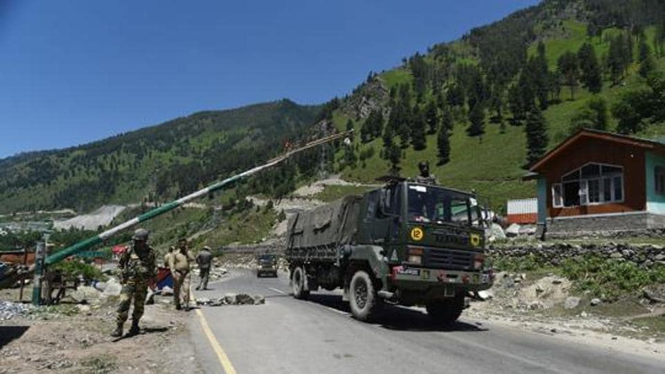 An Indian Army convoy crosses a checkpost in Gagangeer along a highway leading to Ladakh, in Ganderbal, Jammu and Kashmir,