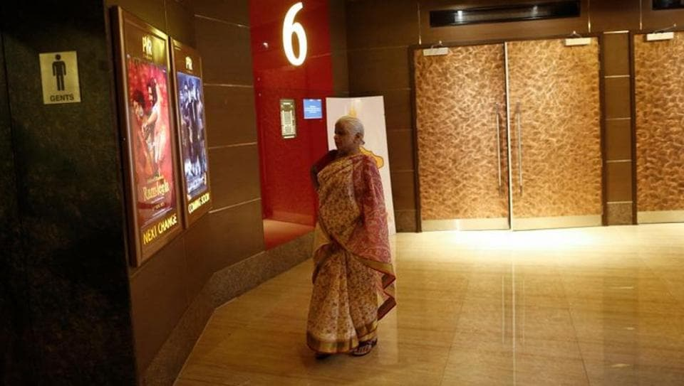 A woman looks at posters of Bollywood films at the lobby of a PVR Multiplex in Mumbai November in file photo.