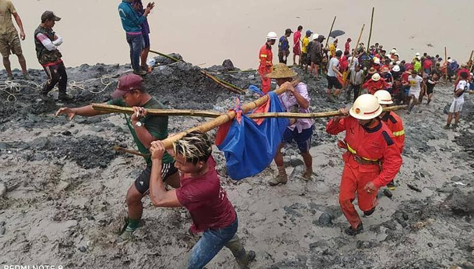 In this photo released from Myanmar Fire Service Department, rescuers carry a recovered body of a victim in a landslide from a jade mining area in Hpakant, Kachine state, northern Myanmar Thursday, July 2, 2020.