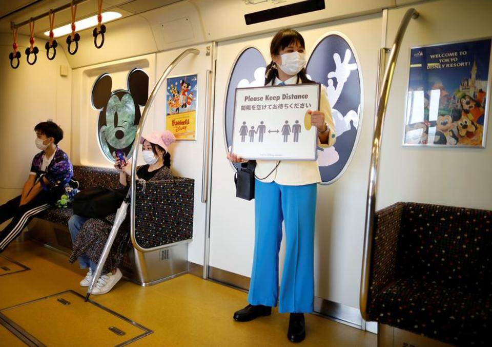 A staff member holds a sign to remind visitors to practice social distancing before the reopening of Tokyo Disneyland along with Tokyo DisneySea, which closed for months due to the coronavirus disease (COVID-19) outbreak, at a Disney Resort line train in Urayasu, east of Tokyo, Japan July 1, 2020.  (REUTERS)
