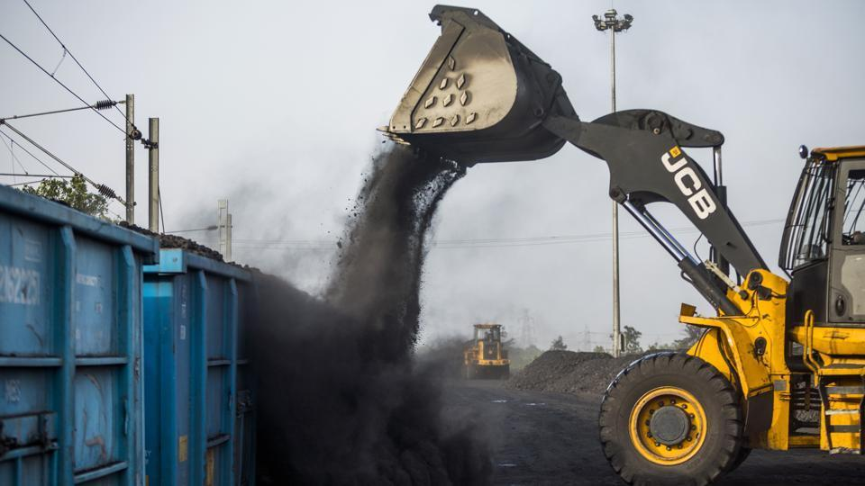 A JC Bamford Excavators Ltd. (JCB) front loader loads coal onto a freight wagon at the Tori Siding on the Tori-Shivpur rail line, operated by Indian Railways and funded by Coal India Ltd., in Chandwa, Jharkhand.
