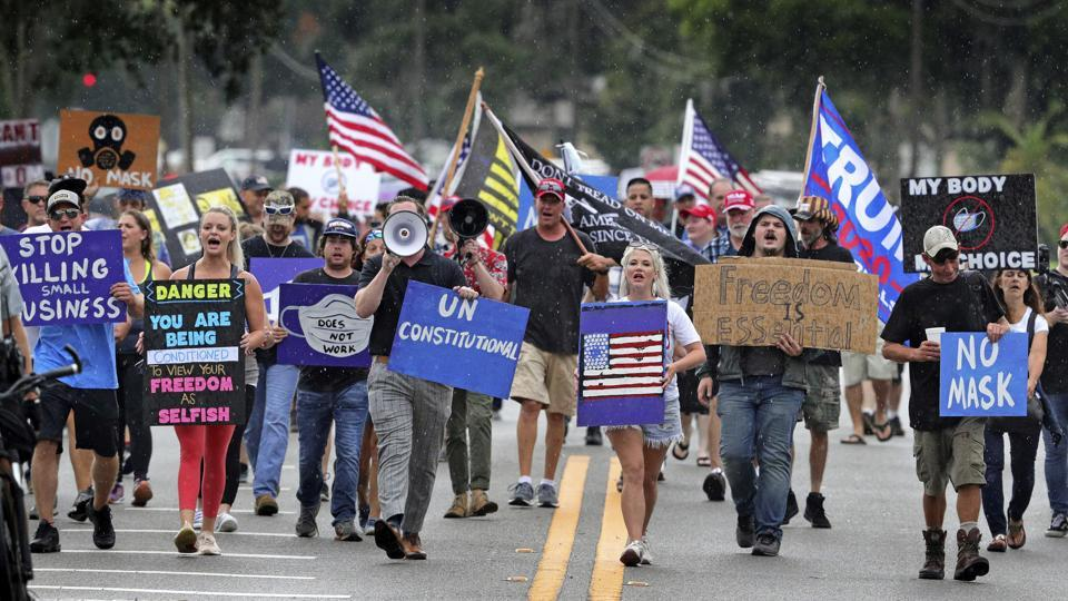 Demonstrators march through downtown Sanford to protest a government order mandating masks while inside a business or when attending public gatherings indoors, in Florida on July 1. The US saw Covid-19 cases rise by over 50,000 yesterday, according to the worldometers tracker, marking the biggest one-day spike in the country since the start of the pandemic. (Joe Burbank / Orlando Sentinel via AP)
