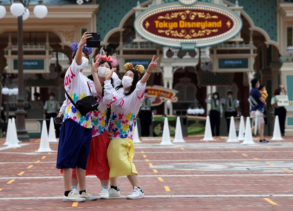 Visitors take a photo after the reopening of Tokyo Disneyland along with Tokyo DisneySea, which closed for months due to the coronavirus disease (COVID-19) outbreak, at the entrance gate of Tokyo Disneyland in Urayasu, east of Tokyo on Wednesday.  (REUTERS)