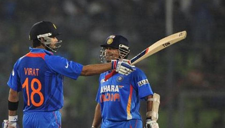 Virat Kohli raises his bat as Sachin Tendulkar watches.