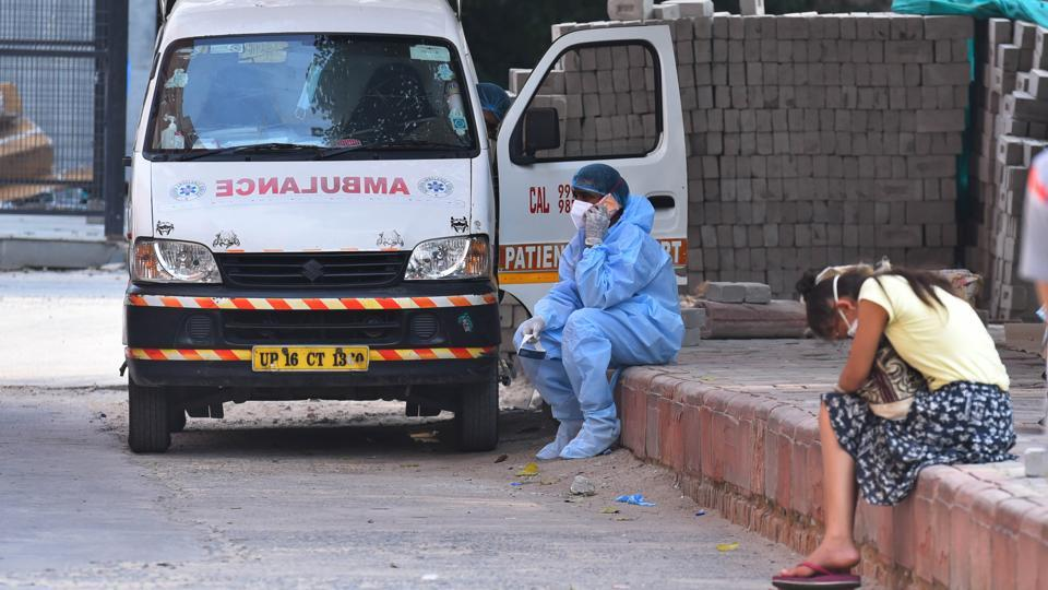 "A medical professional in PPE overalls talks on the phone while waiting to transport people outside the Covid-19 ward at Lok Nayak Jai Prakash Hospital on July 1. Delhi CM Arvind Kejriwal in his media briefing on the same day said, ""There was a day when nearly 125 deaths were recorded. Today, the daily Covid deaths are hovering around 60-65. We have to reduce this further,"" (Raj K Raj / HT Photo)"
