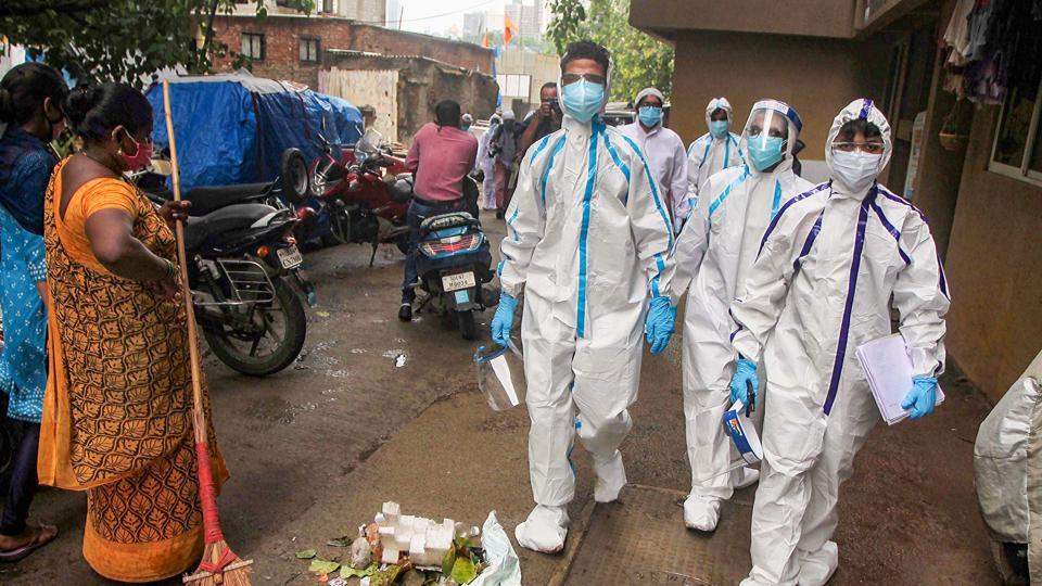 Healthcare workers wearing PPE suits arrive to carry out medical checkups of the residents living in the COVID-19 hotspot areas, at Malad in Mumbai on Thursday.