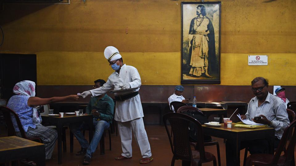 A server wearing a face mask and gloves attends to customers at the Indian Coffee House on College Street in Kolkata on July 2. One of the city's most loved eateries, the Coffee House had to shut its doors over three months ago because of the coronavirus lockdown imposition in the whole country. (Samir Jana / HT Photo)