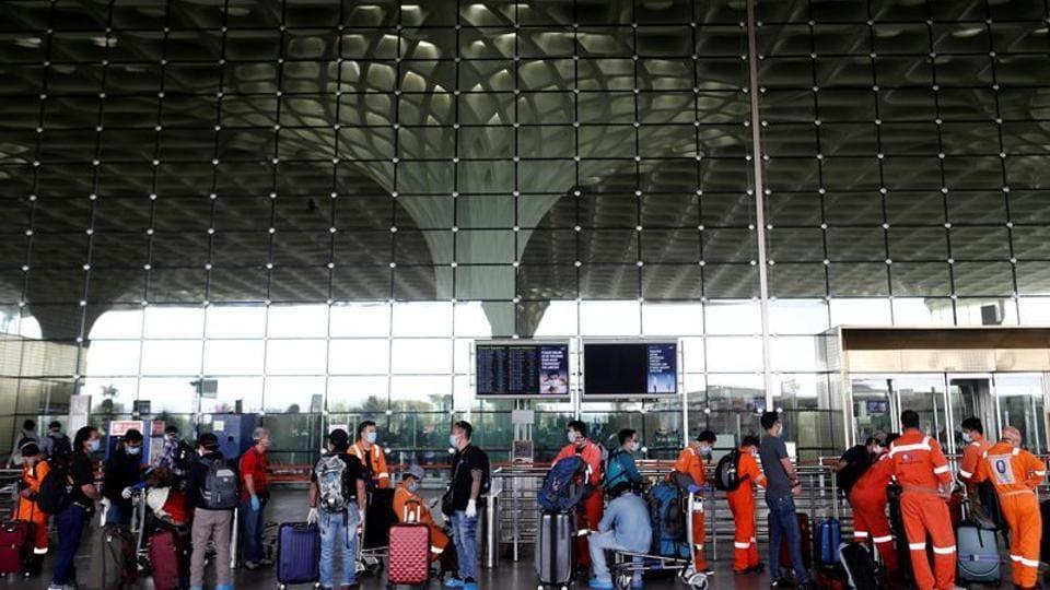 Passengers wearing protective face masks wait in a queue to enter Chhatrapati Shivaji International Airport in Mumbai, India.