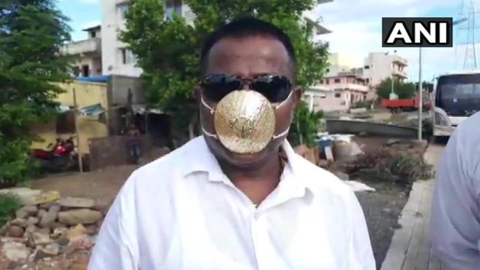 The image shows Shankar Kurade, a resident of Pune, wearing a gold mask.