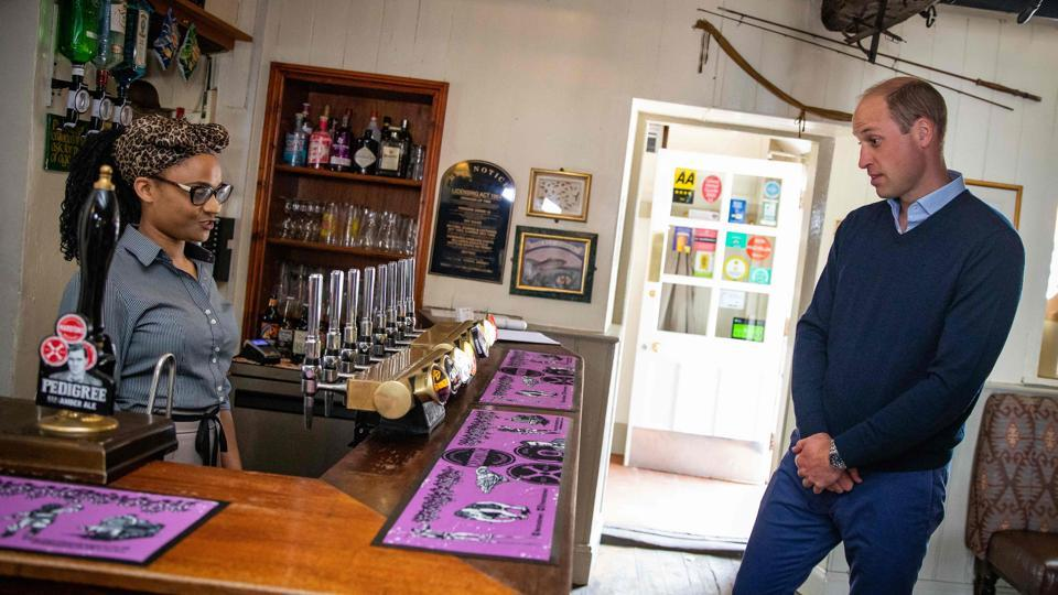Britain's Prince William, Duke of Cambridge (R) chooses a drink at the bar of The Rose and Crown pub in Snettisham on July 3. Restaurants, hotels, cinemas and hairdressers in England reopened their doors for the first time yesterday after three months of lockdown due to Covid-19. (Aaron Chown / AFP)