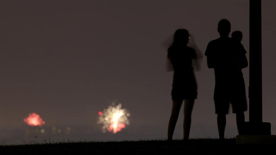 People watch distant Fourth of July fireworks, Friday, July 3, 2020, from a park in Kansas City, Mo. (AP)