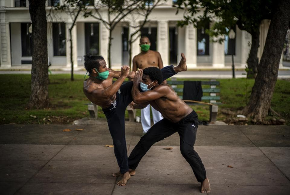 Wearing protective face masks as a precaution against the spread of the new coronavirus, Victor Rafael Torres, left, and Eiver Carbonell train in capoeira in a park while his teacher Misael watches them, after an easing of COVID-19 related lockdown restrictionsin Havana, Cuba, Friday, July 3, 2020.