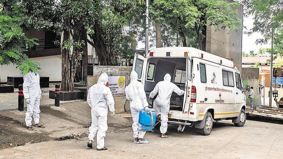 Contract workers at Yerawada crematorium on Saturday. The Pune Municipal Corporation has allotted only six ambulances to transport Covid-19 dead bodies.