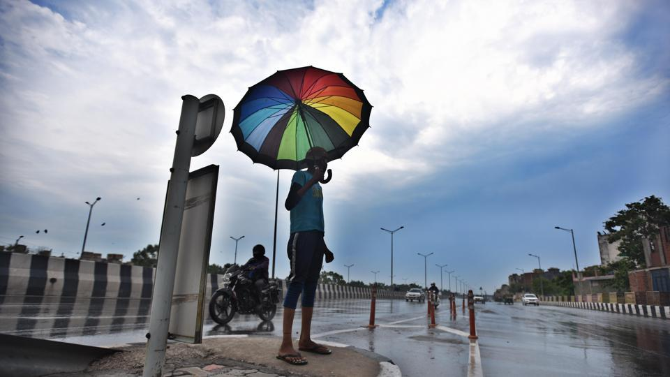 A man uses an umbrella to take shade from the rain, at NH-24, in New Delhi, India, on Thursday, June 25, 2020.