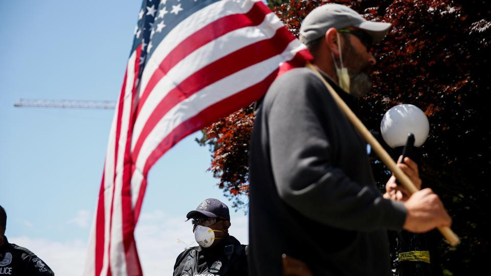 A man holding an American flag walks by Seattle Police officers guarding a closed Cal Anderson Park in the former Capitol Hill Occupied Protest (CHOP) area on the Fourth of July holiday in Seattle, Washington, U.S. July 4, 2020.