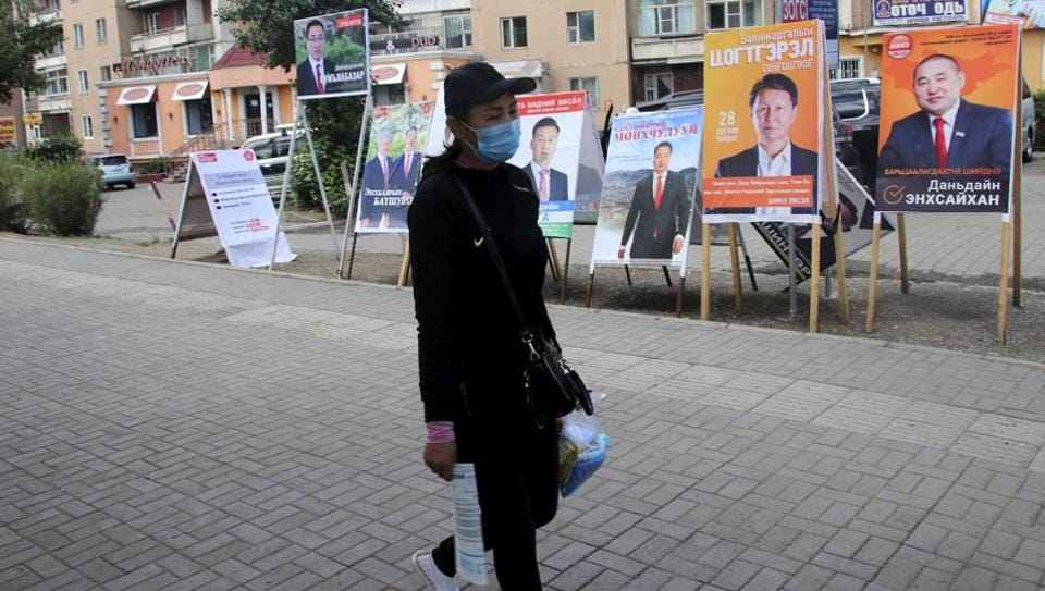 A resident carries groceries past posters and stands in the Songinokhairkhan district on the outskirts of Ulaanbaatar, Mongolia.