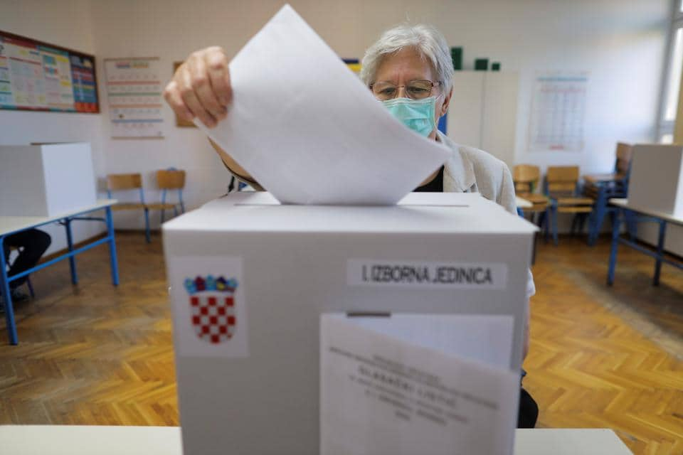 A person wearing a face mask casts a ballot during parliamentary elections, amid the spread of the coronavirus disease (Covid-19), in Zagreb, Croatia, July 5, 2020.