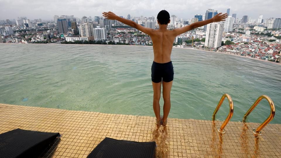 A boy jumps into the water at the gold-plated infinity pool of the newly inaugurated Dolce Hanoi Golden Lake luxury hotel, after the government eased a nationwide lockdown following the global outbreak of the coronavirus disease (COVID-19), in Hanoi, Vietnam. (REUTERS/Kham)