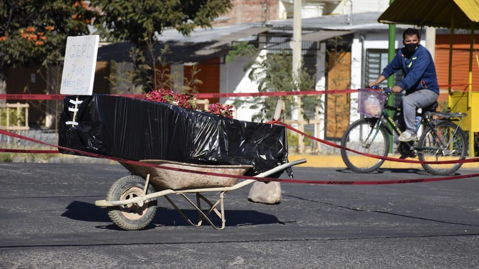 A coffin wrapped in plastic holding the remains of an unidentified men, who died last week, sits on a wheelbarrow in the middle of a street, placed there by his family to draw attention of the authorities to show that his remains are yet to be collected, in Cochabamba, Bolivia on Saturday.