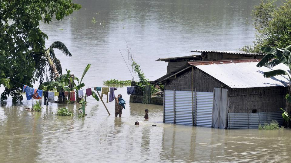 A woman dries clothes as others swim in a flooded area of Morigaon, Assam, July 1. It is time the central and the state governments prepare a long-term plan that goes beyond piecemeal measures like building embankments and dredging to control floods