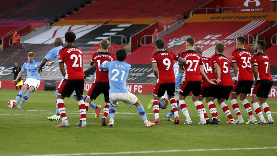 Manchester City's Kevin De Bruyne, left, takes a free kick during the English Premier League soccer match between Southampton and Manchester City at St. Mary's Stadium in Southampton, England, Sunday, July 5, 2020. (AP Photo/Frank Augstein,Pool)