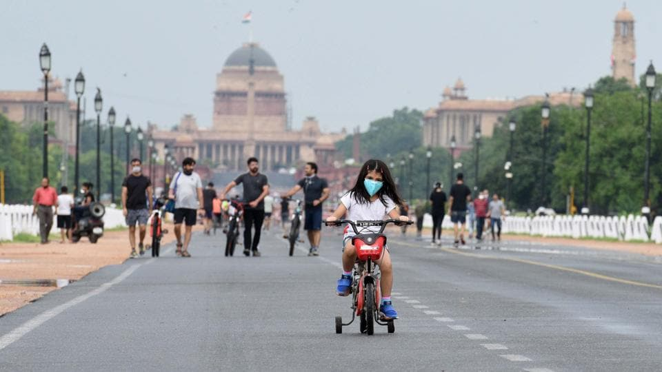 New Delhi, India - July 5, 2020: A girl rides a bicycle at Rajpath after rain showers in New Delhi, India, on Sunday, July 5, 2020.
