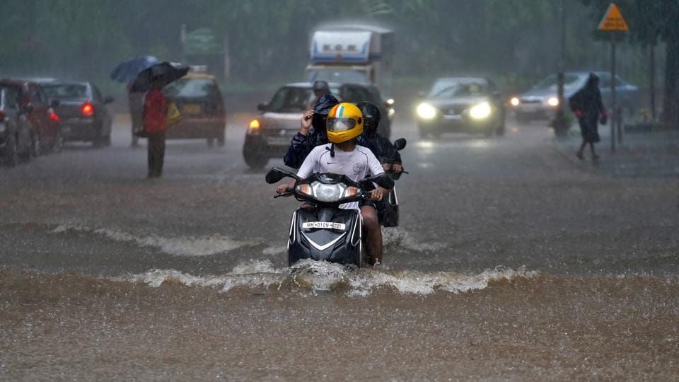 People ride their scooters through a water-logged road during heavy rains in Mumbai, India.